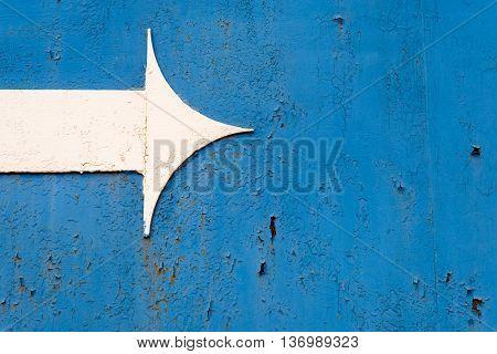 White Metal Arrow On Rusted Blue Metal