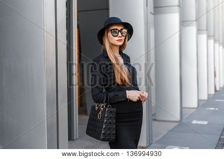Beautiful Stylish Young Business Woman In A Hat And Sunglasses With A Handbag