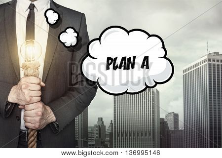 Plan A text on speech bubble with businessman holding lamp on city background
