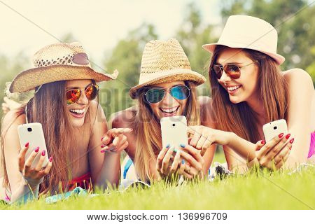 Picture showing happy group of friends lying on the grass and texting