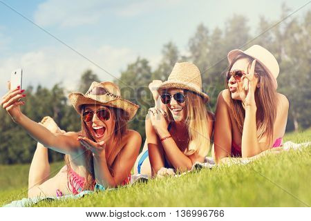 Picture presenting a group of women in bikin taking selfie outdoors