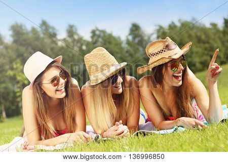 Picture presenting a group of women in bikin showing something outdoors