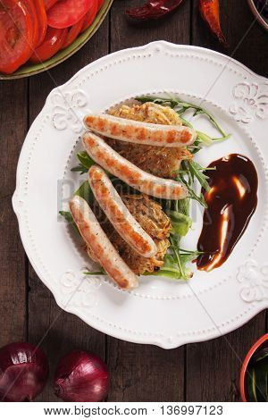 Grilled sausage served over hash browns with rocket salad and barbecue sauce