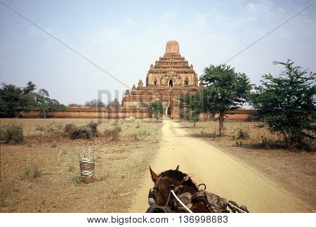 Approaching the ancient Sulamani Buddhist Temple, in Pagan, Burma (now called Myanmar), via horse-drawn carriage across a dirt road, circa 1987.