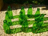10 green bottles in the form of a number 10 sitting on a wall, depicting a UK nursery rhyme. poster