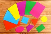 Colorful cardboard geometric shapes. Cut from cardboard triangle, square, oval, trapezoid, rectangle, circle. Children education concept. Sheets of colored paperboard on a wooden table poster