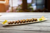 Long plate with sushi rolls. Sushi plate on wooden surface. Delicious low-calorie food. Hosomaki rolls and marinated ginger. poster