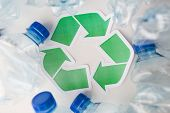 waste recycling, reuse, garbage disposal, environment and ecology concept - close up of used plastic water bottles with green recycle symbol on table poster