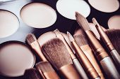Professional makeup brushes and tools, natural make-up products set, eyeshadows and concealers on white table. poster