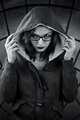 Sinister black and white portrait. Girl in the hood with gaze over her glasses and skull tattoo on the finger. On abstract dark stained-glass background poster