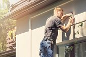 young electrician installing lamp on house facade poster
