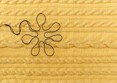 Yellow Knitted Background with Pattern and Braids and Blue Flower.Hand Made;Fancywork. poster