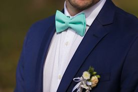 Groom set the bowtie straight close up