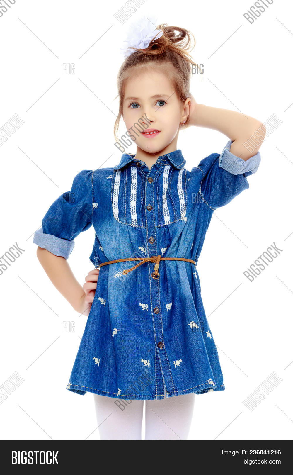9ee64fa91ca The little blonde girl with a large white bow on the head and short denim  dress.She holds a finger to his cheek.Isolated on white background.