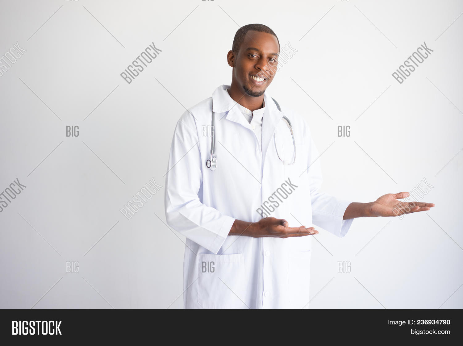843165c97ab Happy black male doctor pointing at empty space and presenting service.  Medical service advertising concept. Isolated front view on white background .