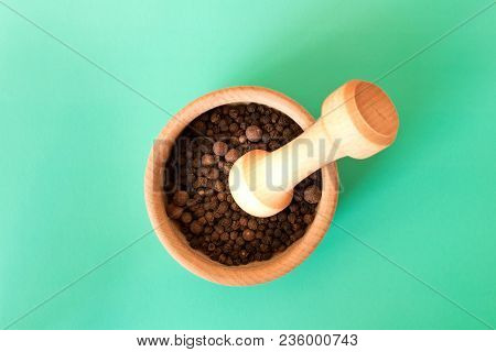 Mortar With Black Pepper And Pestle . Isolated On Turquoise Background .