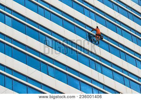 Industrial Climber Wash The Windows Of Skyscraper.  A Modern Skyscraper.