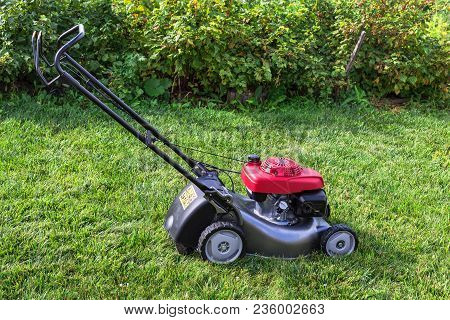 Lawn Mower On A Green Lawn On A Summer Day.