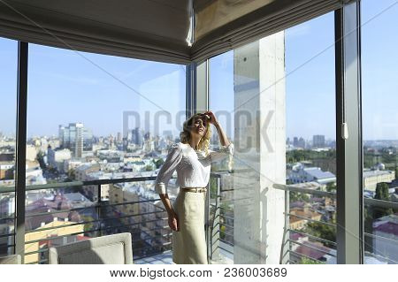 Gorgeous Woman Standing At Restaurant Near Window With Buildings In Background. Concept Of Catering