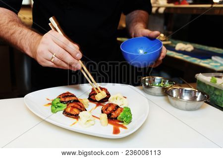 Chef is decorating fusion style dish using chopsticks, copy space, toned image