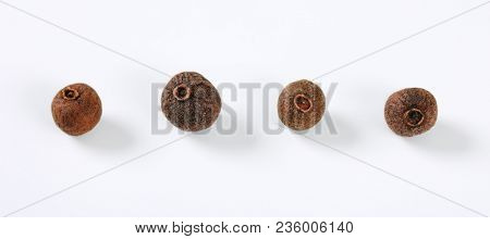whole allspice berries on white background