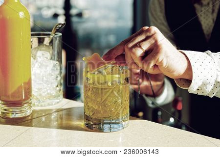 Bartender is decorating a drink with piece of beeswax, toned photo