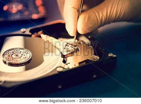 Closeup of hands with tweezers and computer hard disk