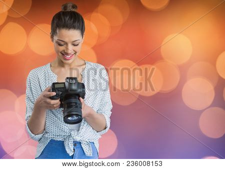 photographer looking the photos on camera. Blue and orange bokeh background