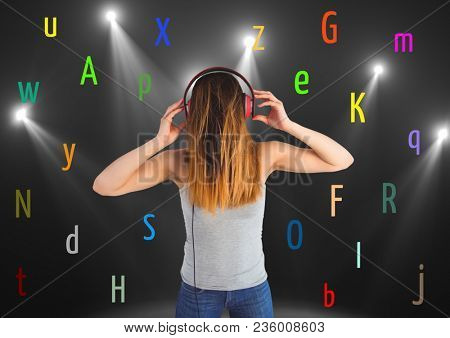 young woman listening music with colour letters around. Black back