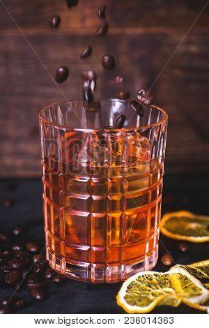 Grains Of Coffee Fall Into A Glass With A Drink. A Glass With Whiskey On A Wooden Background. Close-