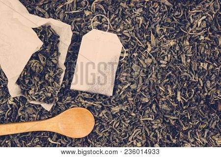 Paper Tea Bags And Wooden Spoon On Dry Tea As Background