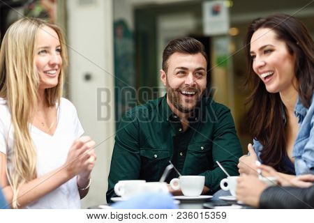 Multiracial Group Of Friends Having A Coffee Together. Two Women And A Man At Cafe, Talking, Laughin