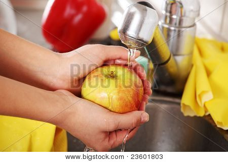 Woman hands washing tasty apple
