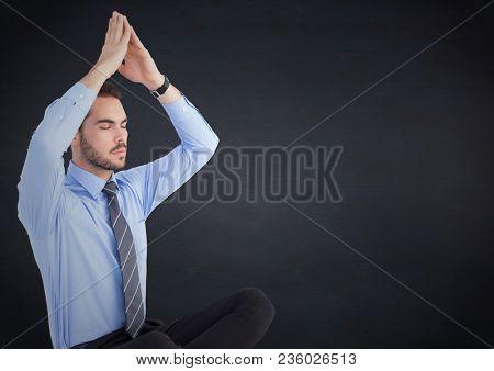 Business man meditating against navy chalkboard