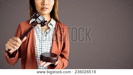 Female judge with gavel against brown background