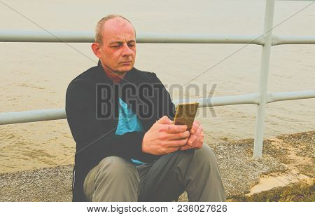 Midle aged man sitting on the shore of the lake. Solitude mature man using mobile phone on the bank. Concept of activ man. poster
