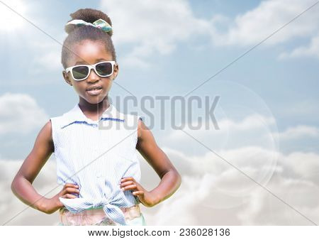 Girl in sunglasses hands on hips against sky with flare