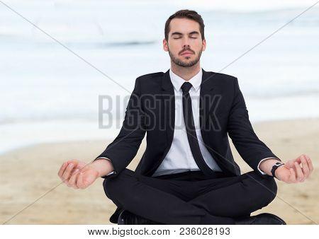 Business man meditating against blurry beach