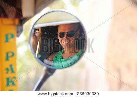 Reflection In A Circular Mirror. The Male Face Is Reflected In The Mirror Of The Tuk Tuk. A Tourist