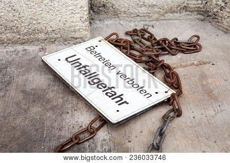 Sign Lying On Floor With German Words No Trespassing Accident Hazard