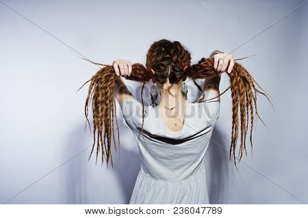 Studio Shoot Back Of Girl In Gray Dress With Pigtails Dreads On White Background.