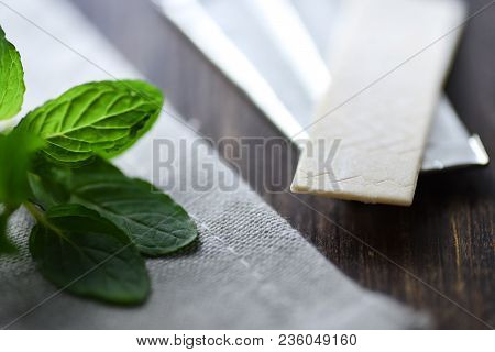 Chewing Gums With Mint Leafs On Wooden Table Close Up