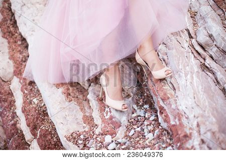 Bride`s Two Legs In High-heeled Shoes Under Pink Wedding Dress With Fluffy Skirt Of Tulle. Bride Sit