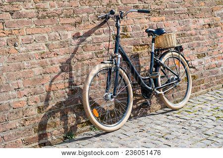 Black Retro Vintage Bicycle With Old Brick Wall.