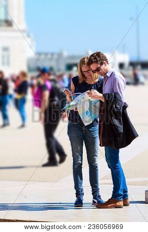 Lisbon, Portugal - March 27, 2018: Tourists Couple Looking At City Map And Travel Guide At The Squar