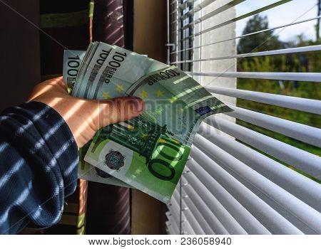 Hand Holds Euro Money Near Pvc Window With Jalousie