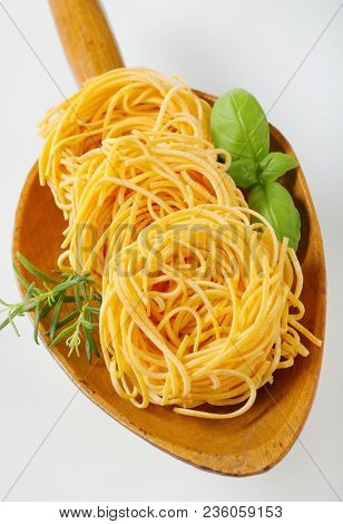 bundles of spaghetti pasta and herbs in wooden scoop