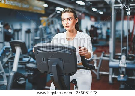 Indoor Cycling Woman Doing Hit Cardio Workout Biking On Indoors Gym Bike. Girl Cyclist Working Out I