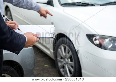 Insurance Agent Examine Damaged Car And Filing Report Claim Form After Accident, Traffic Accident An