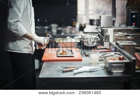 Restaurant Chef Cook Preparing Salmon Filet Flambe. Focus Is On The Salmon, Burner And Cook S Hand.